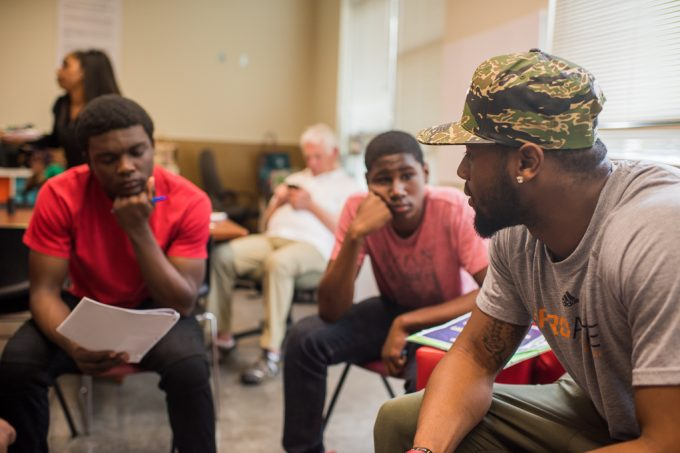 Young African American Man speaks thoughtfully with two teenagers at a group mentoring session